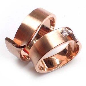 handgemaakte trouwringen in roodgoud met in de damesring een fonkelende diamant