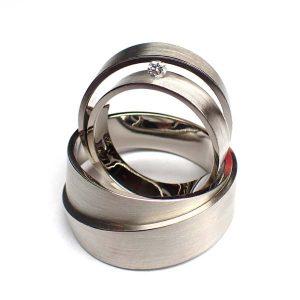 trouwringe in witgoud met een smalle damesring waarin een diamant verwerkt is en een bredere herenring stoer en passend bij de damesring